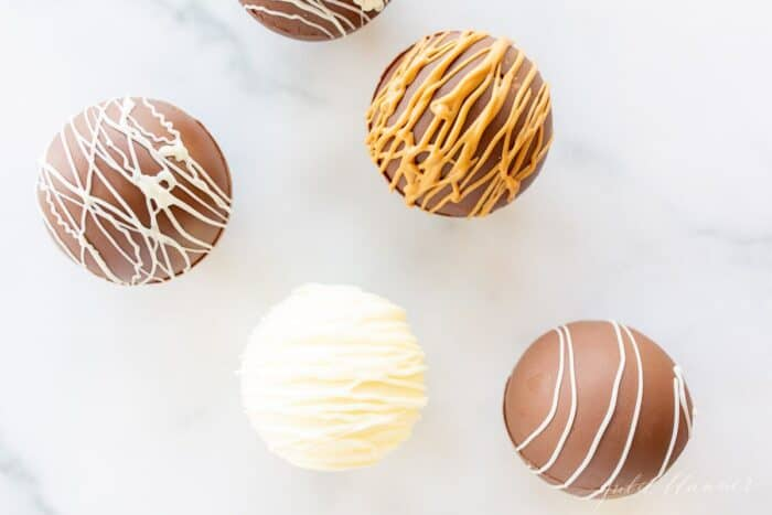Peanut butter hot chocolate bombs on a marble surface, drizzled with peanut butter and white chocolate.