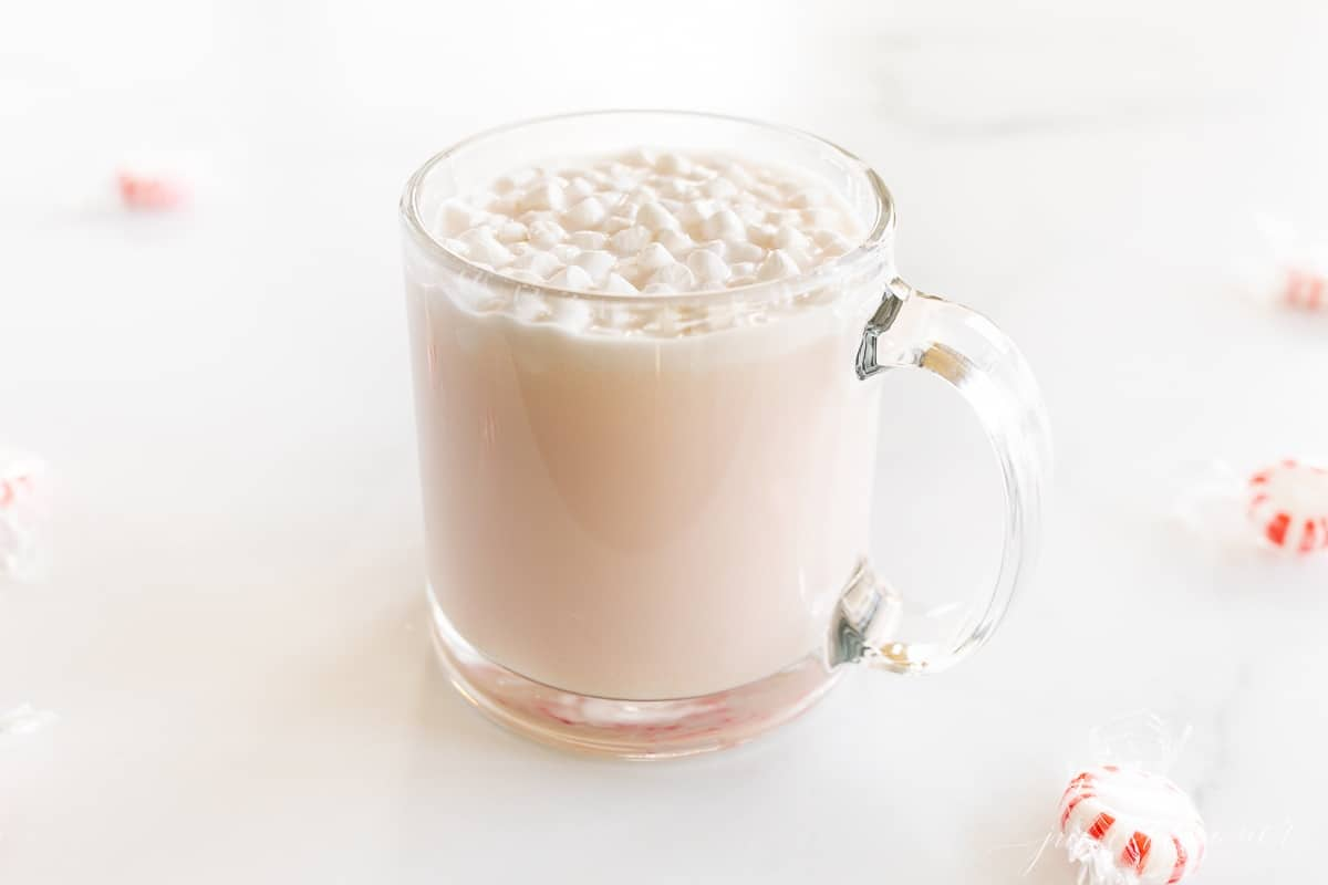A clear glass mug of peppermint hot chocolate, topped with tiny marshmallows and crushed peppermint.