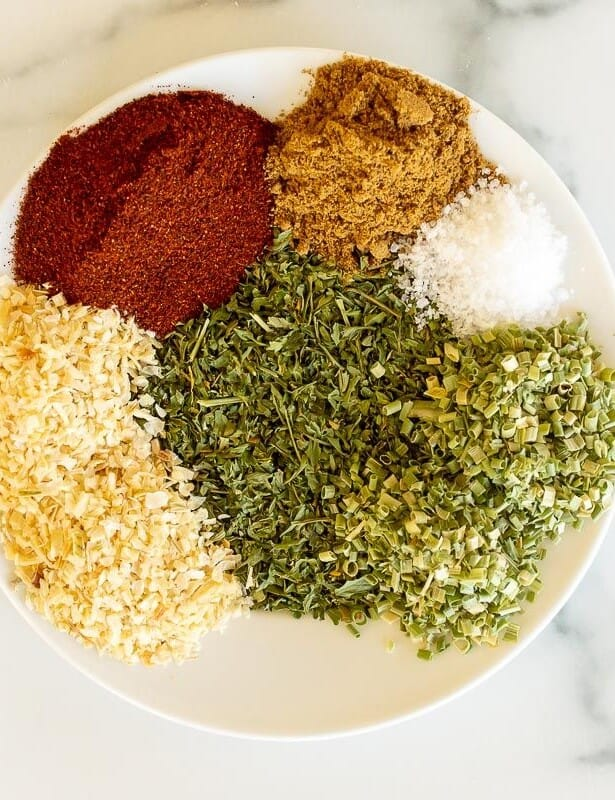 A white plate on a marble surface, topped with individual piles of spices for a homemade fiesta ranch mix.