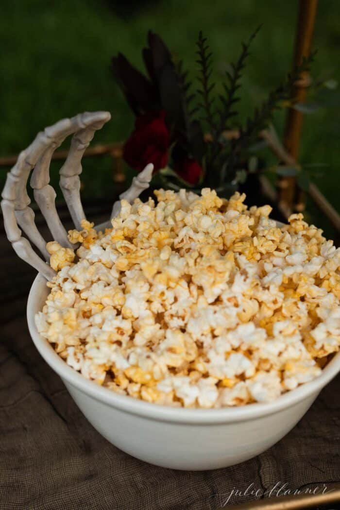 A white bowl full of popcorn with a skeleton hand reaching out for Halloween decorations.