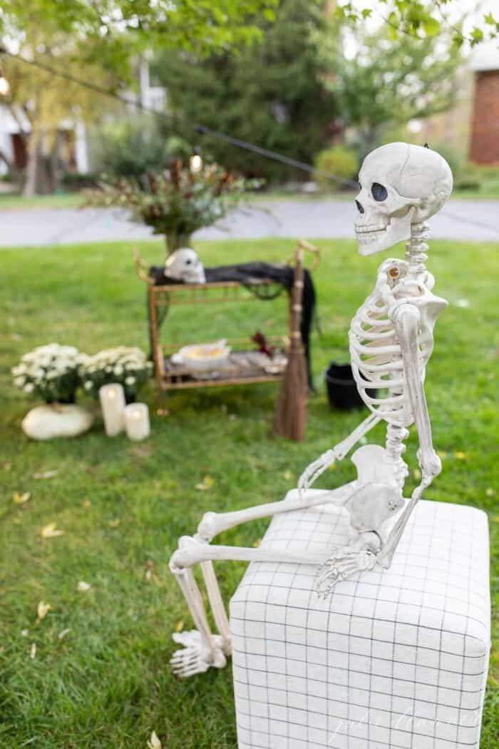 A skeleton sitting on a stool with a Halloween party set up in the background.