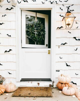 open dutch door surrounded by black bats and pumpkins