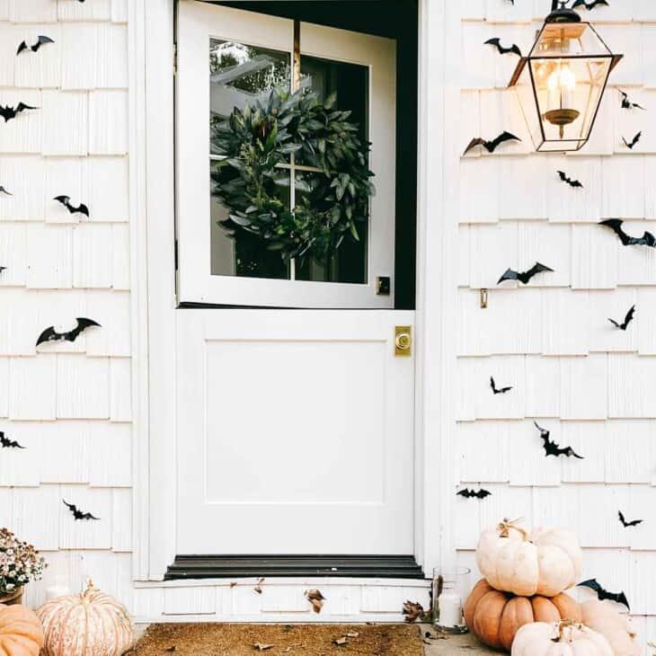 open dutch door surrounded by black bats and pumpkins