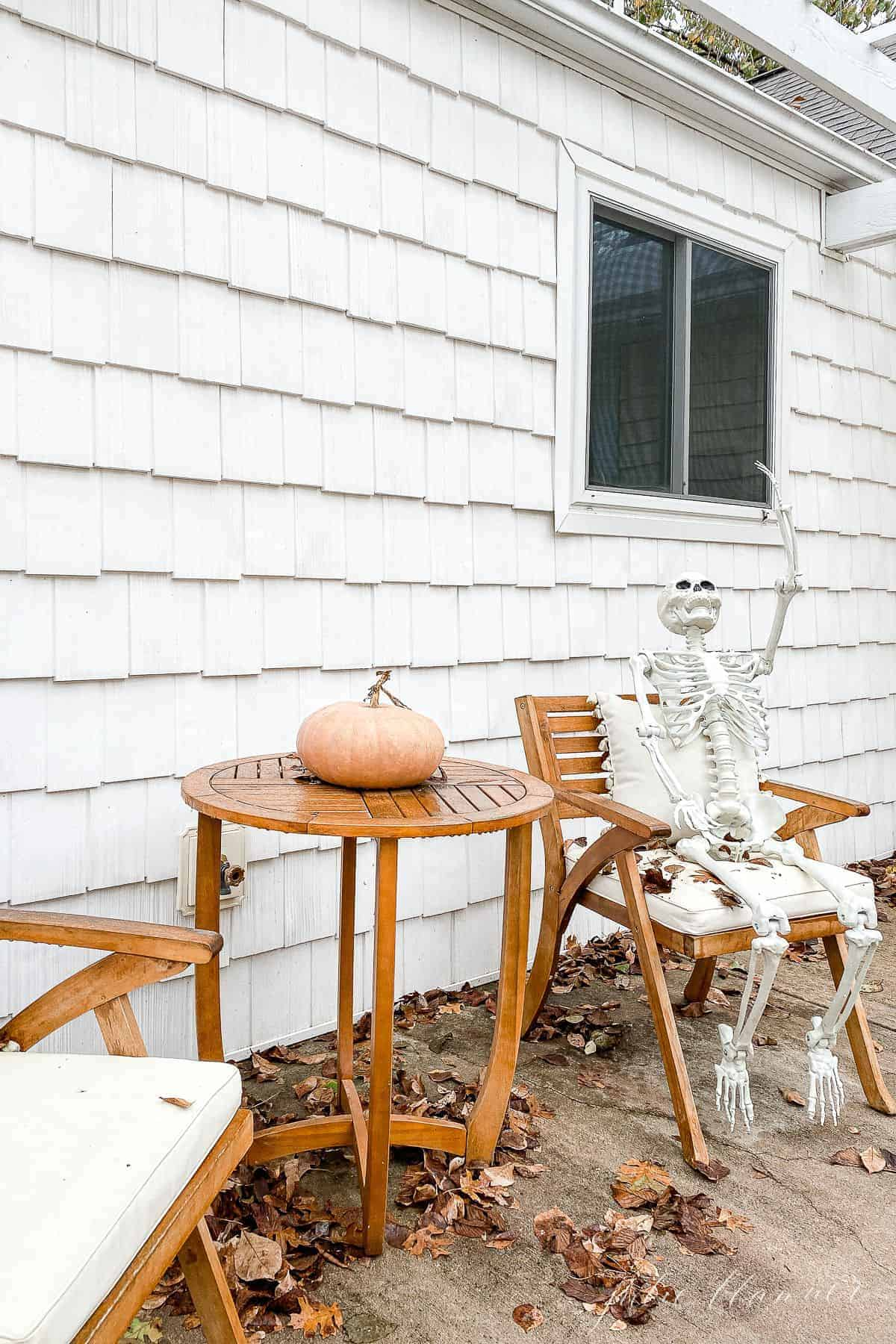 A wooden table set on a front porch with a skeleton waving for Halloween porch decorations.