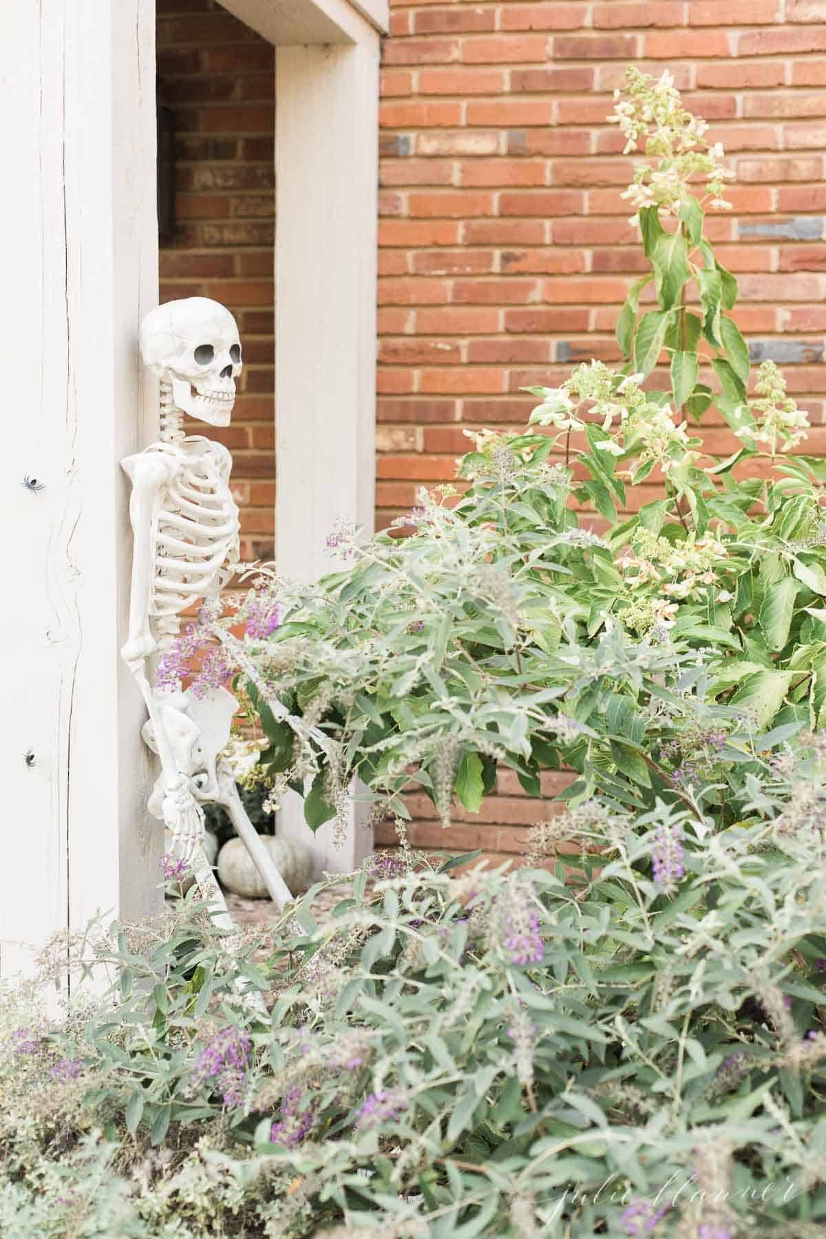 A life size skeleton leaning against a porch pillar for Halloween front porch decor.