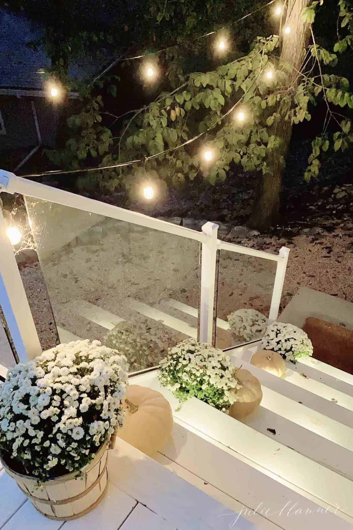 White porch steps with Halloween porch decorations of mums and pumpkins and spider webs