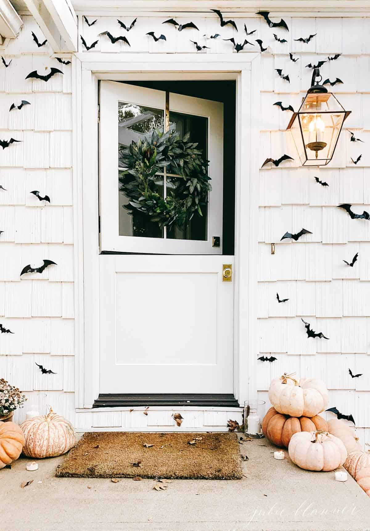 dutch door surrounded by black bats and pumpkins
