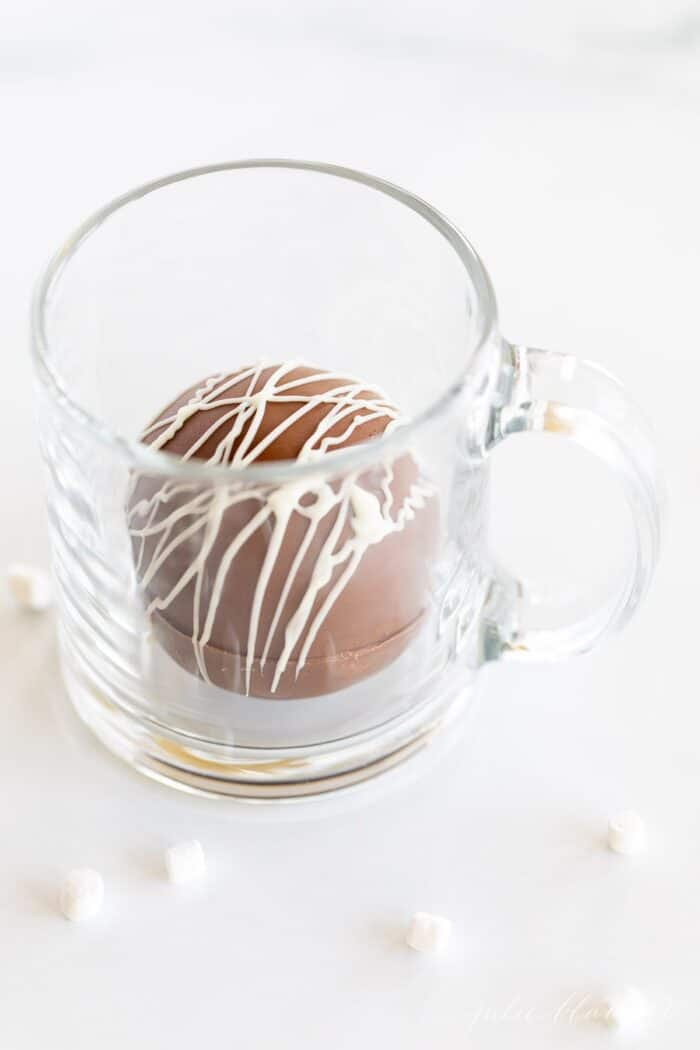 A clear glass mug with a single hot chocolate bomb inside, marshmallows surrounding mug on a marble surface.