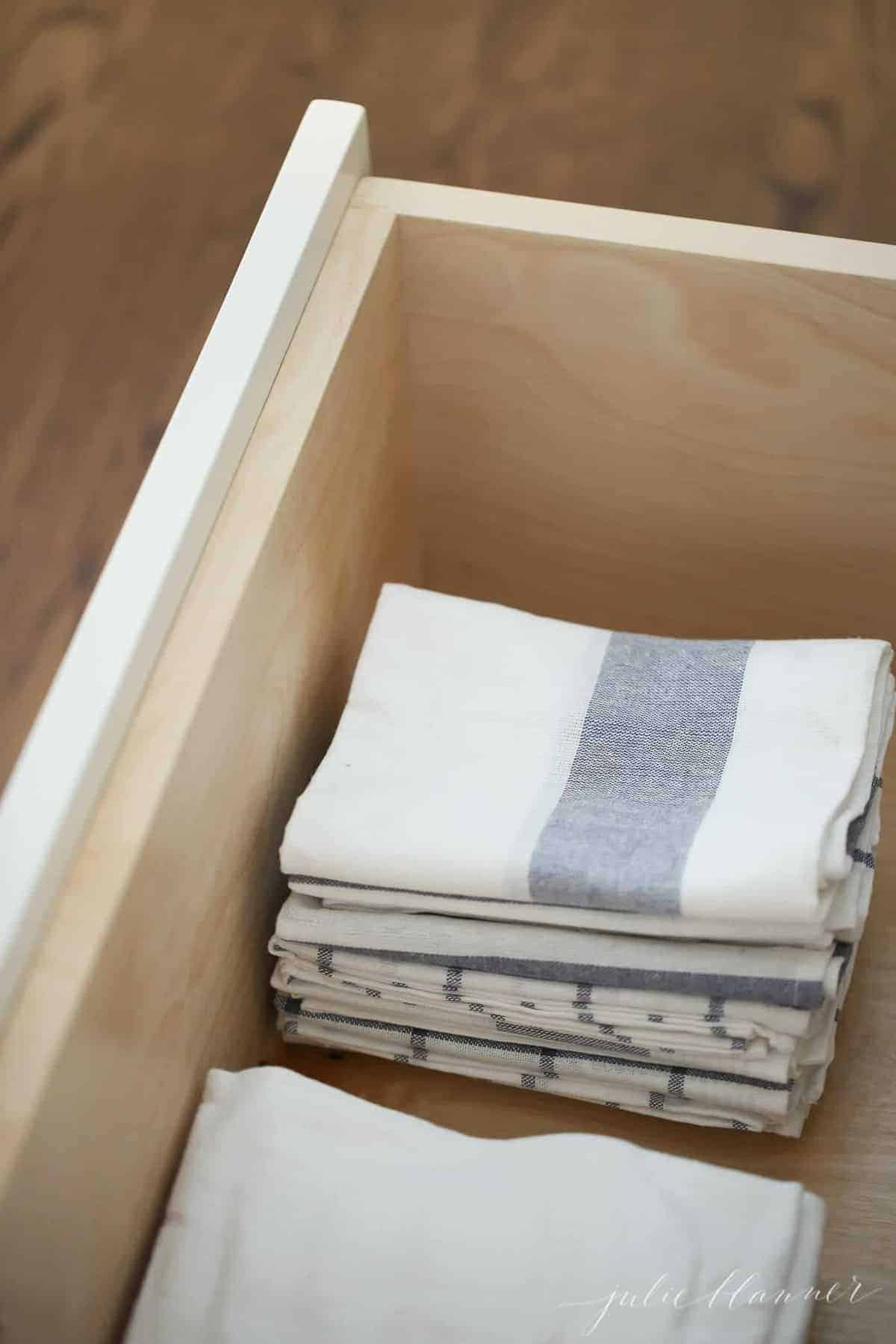 Looking inside a kitchen drawer filled with stacks of striped kitchen towels.