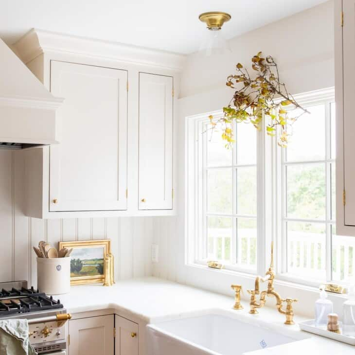 A white kitchen with a fall branch hanging over the kitchen sink window.