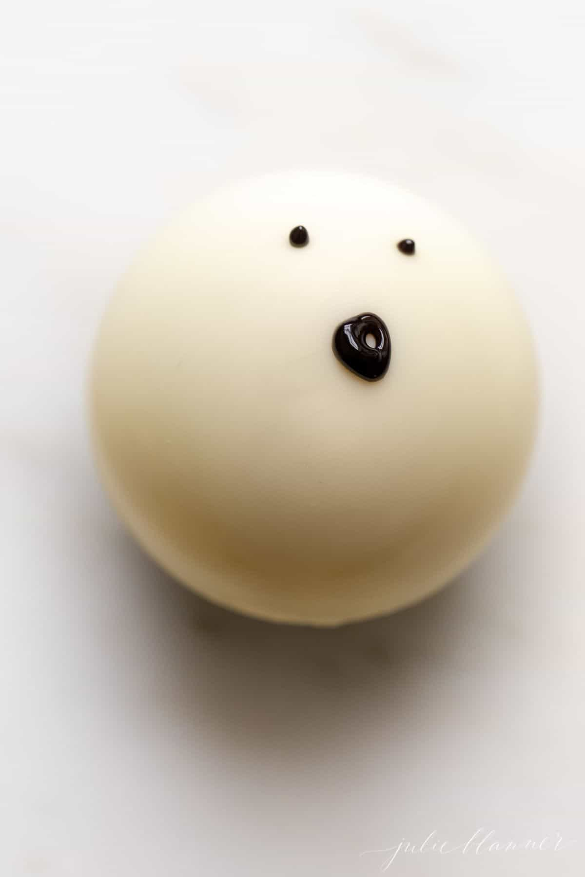 A white chocolate Halloween hot chocolate bomb decorated as a ghost.