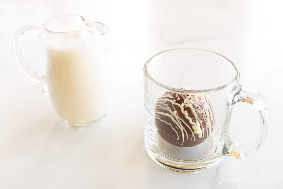A clear glass pitcher of warm milk, clear mug in background, and a hot chocolate bomb.