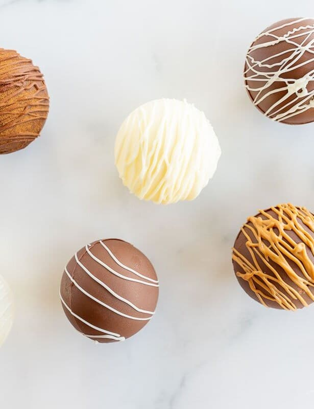 A marble surface with hot chocolate bombs in different colors and decorated styles.