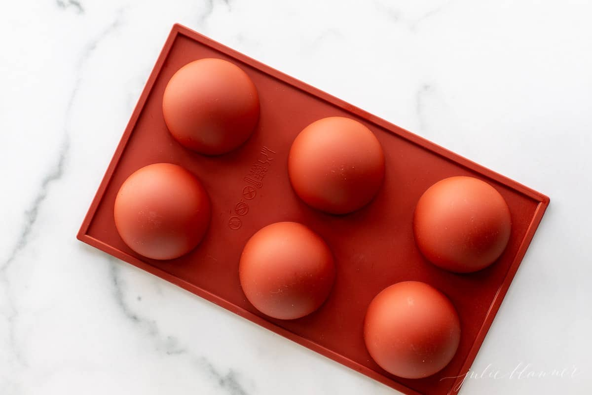 A marble surface with a red silicone sphere mold.