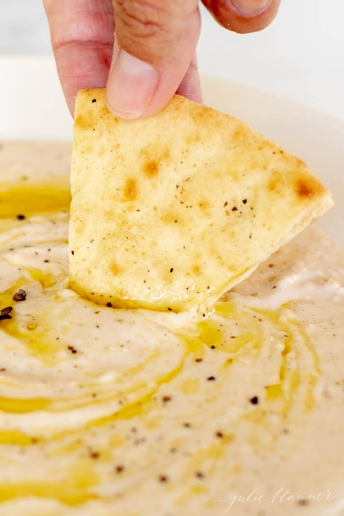A hand dipping a triangle of pita bread into a bowl of white bean dip.