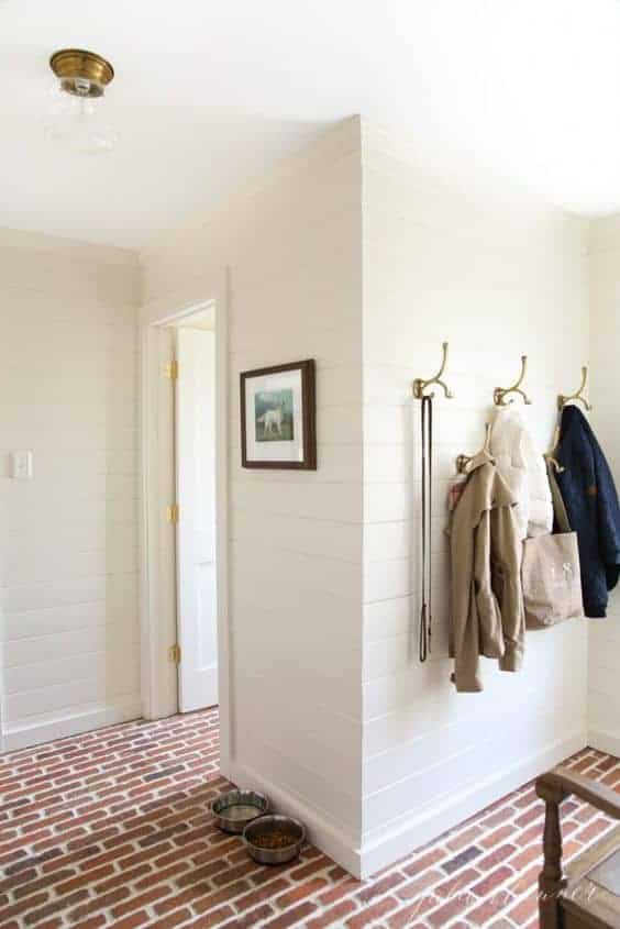 A white mudroom with brick floors and brass hooks