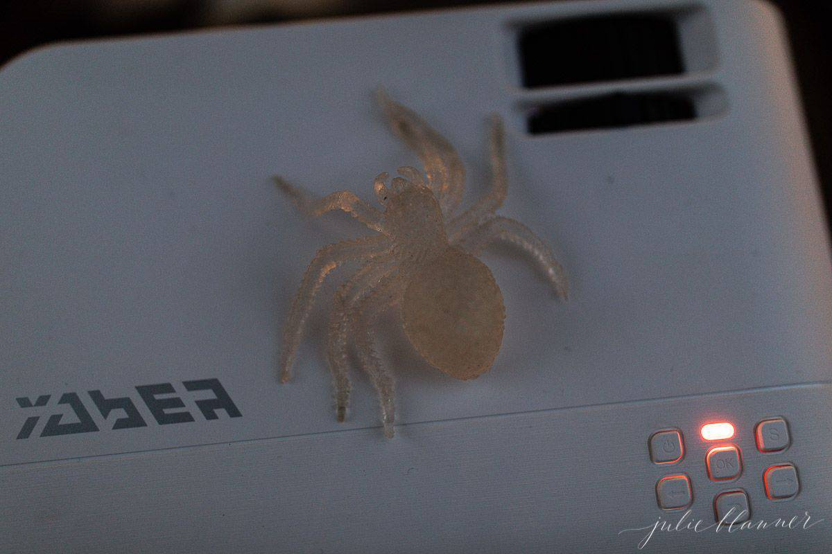 A projector for an outdoor movie night for Halloween, with a plastic spider on top.