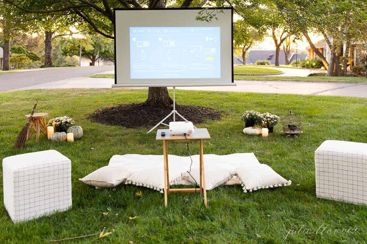 An outdoor movie set up in a yard for halloween, with candles and decorations.