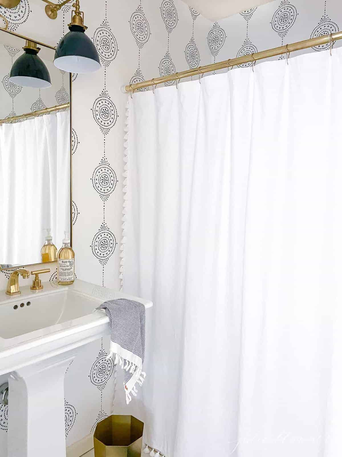 A small bathroom with blue and white wallpaper and a pedestal sink