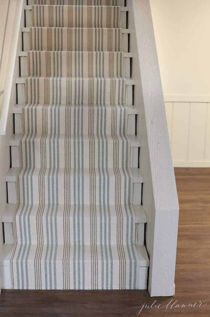 A striped stair runner on basement stairs, made from an indoor outdoor rug.