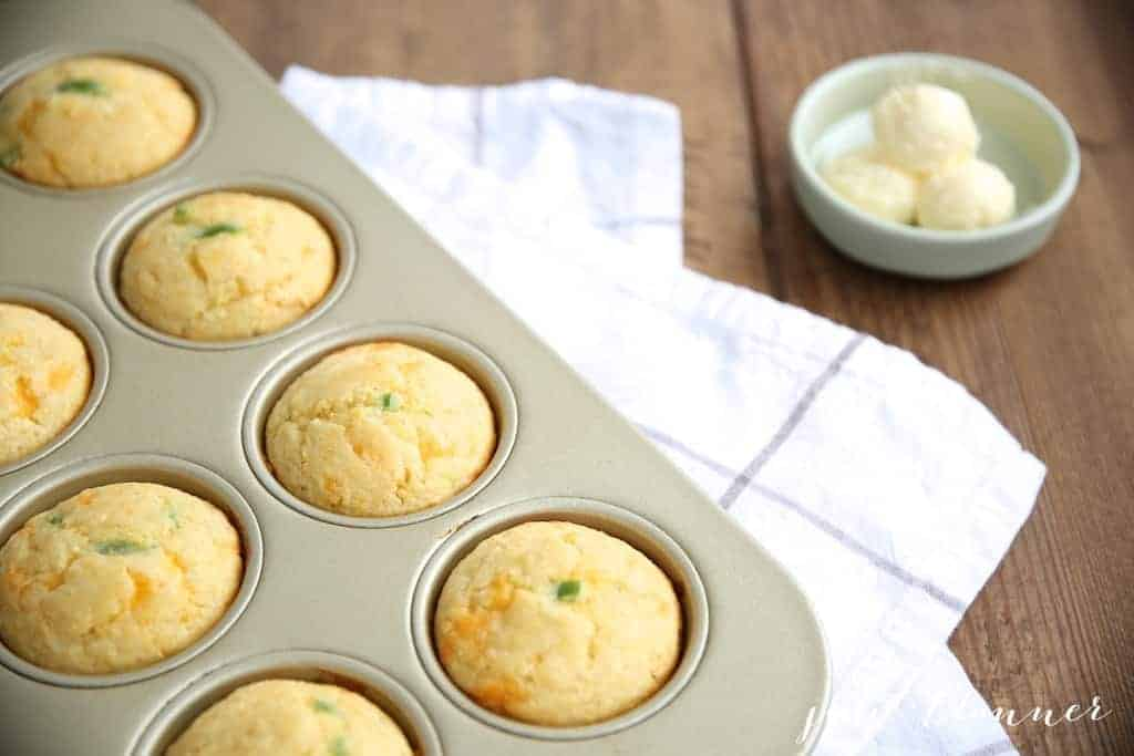 A gold muffin pan full of jalapeno cheddar cornbread muffins, pats of butter to the side