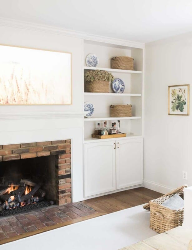 A white living room with a fireplace, built in bookshelves, and a living room rug over hardwood floors.