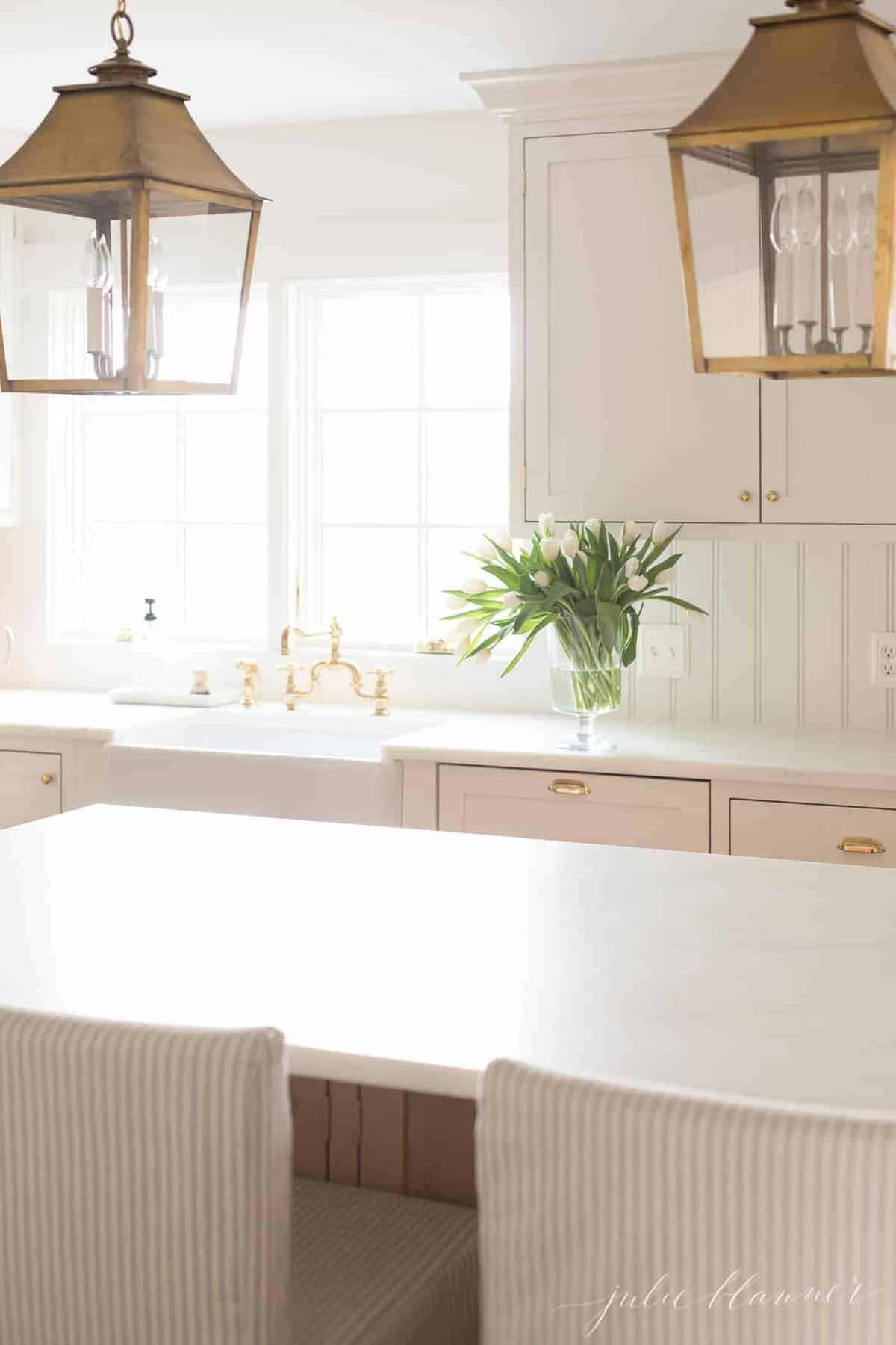 A white kitchen with a large white island, empty minimalist aesthetic with a single glass vase of tulips near sink.