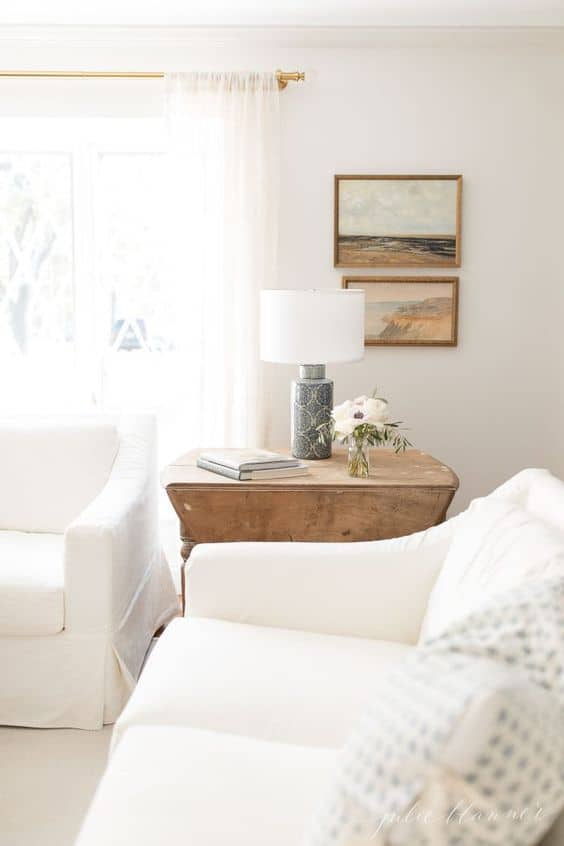 A white living room with two white sofas and a wooden end table.