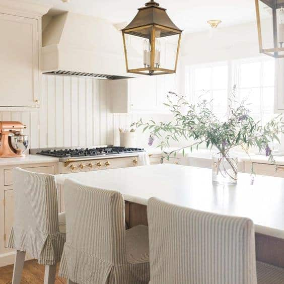 A white kitchen with three barstools and a glass vase of wildflowers.