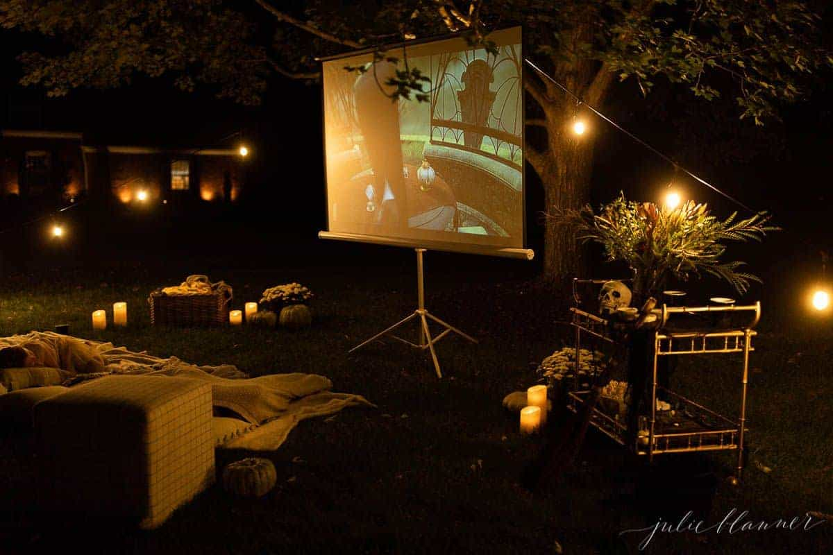 An outdoor movie set up in a yard for halloween, with a skeleton, candles and decorations.