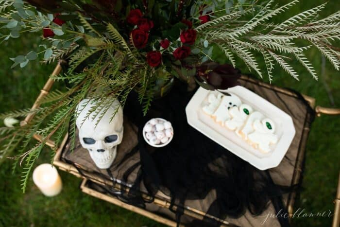 Halloween outdoor movie night snacks set up on a gold bar cart, flowers in the background.