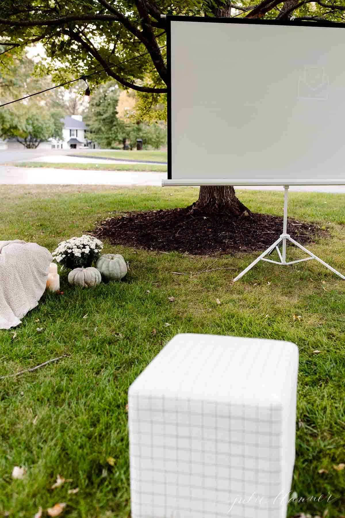 A yard set up with an outdoor movie projector screen in the fall.