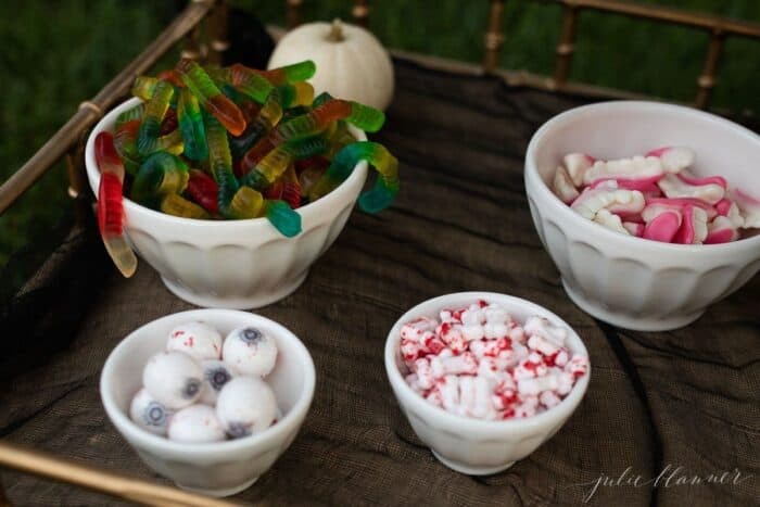 Halloween party snacks set up in white bowls on a gold bar cart.