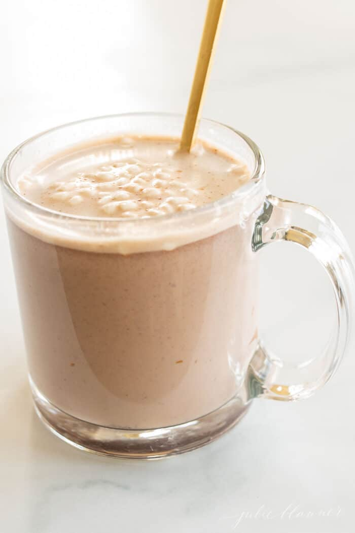 A clear glass mug of peanut butter hot chocolate, gold spoon stirring.
