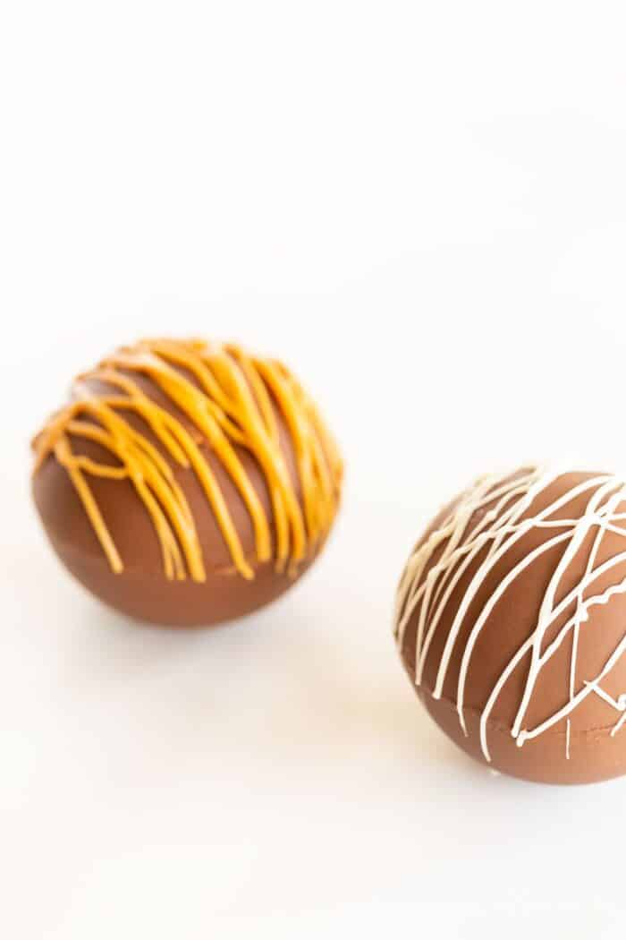 Two peanut butter hot chocolate bombs on a marble surface, drizzled with peanut butter and white chocolate.