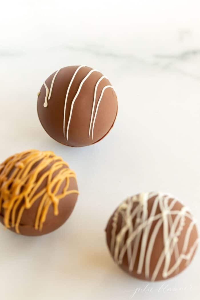 Three peanut butter hot chocolate bombs, drizzled with peanut butter and white chocolate.