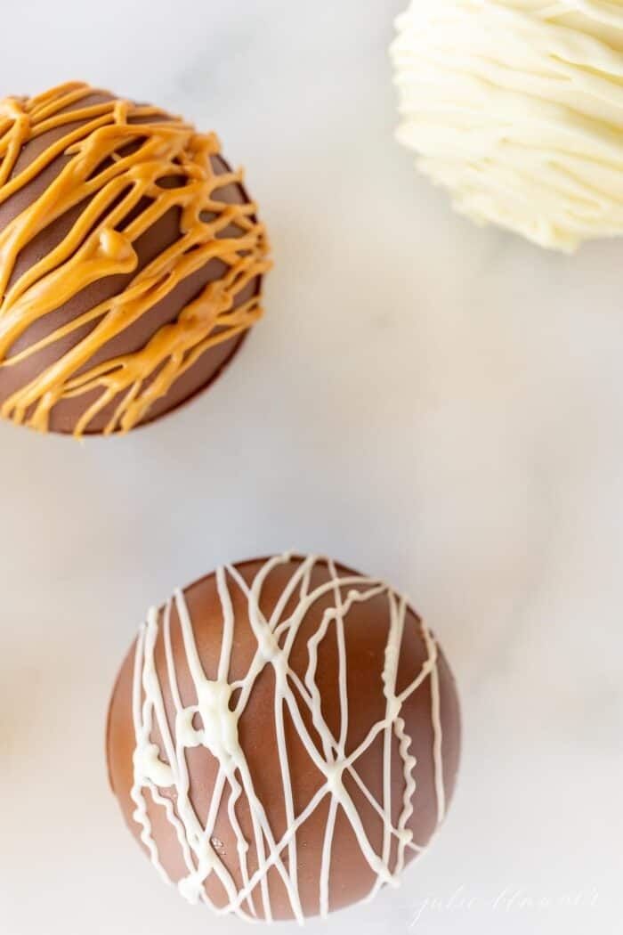 Three peanut butter hot chocolate bombs on a marble surface, drizzled with peanut butter and white chocolate.
