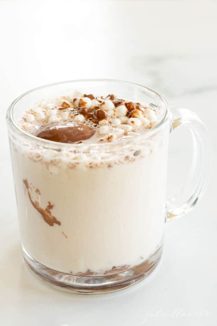 A clear glass mug of peanut butter hot chocolate topped with mini marshmallows.