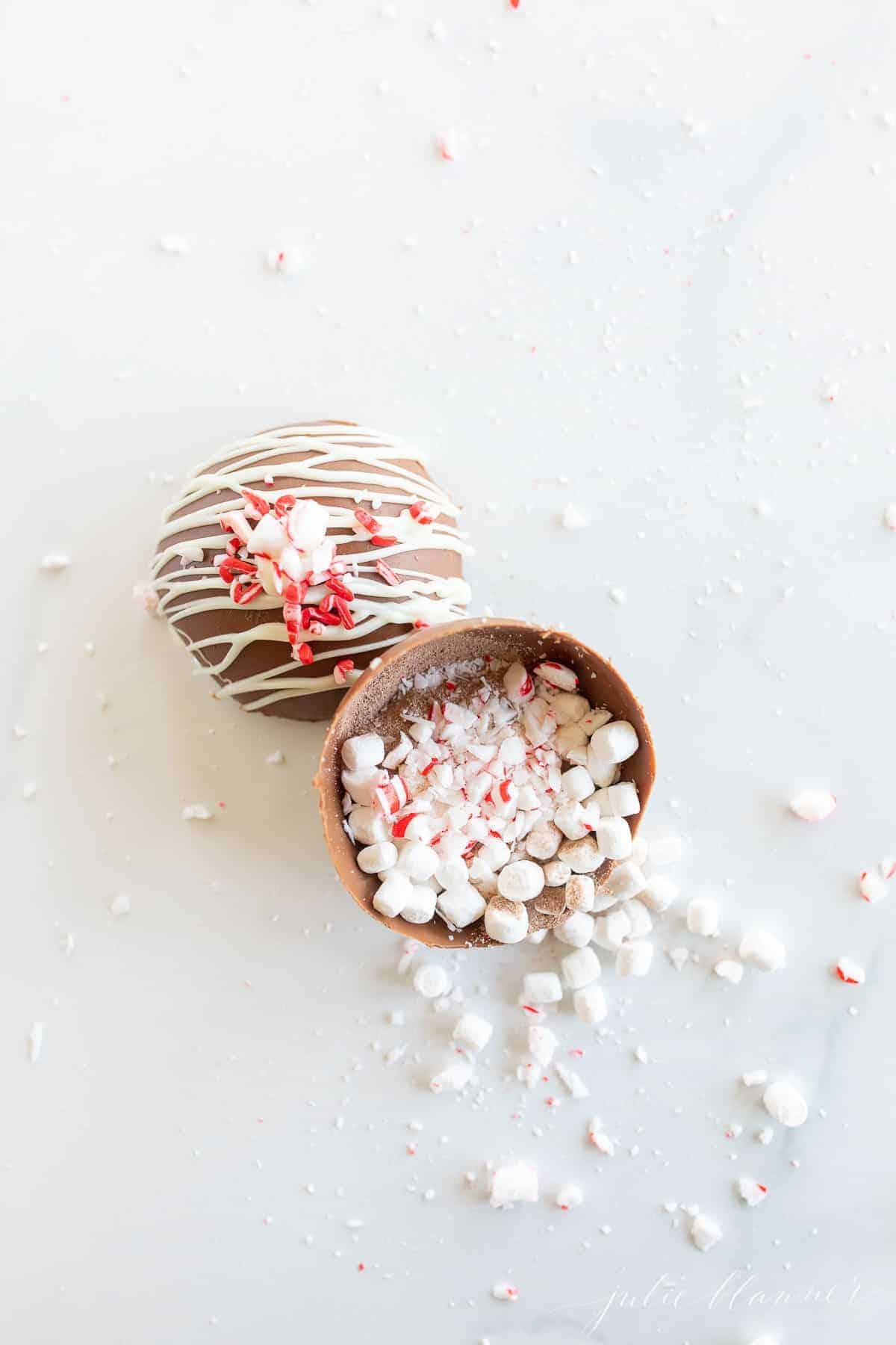 A peppermint hot chocolate bomb, with marshmallows, cocoa mix and peppermint spilling out onto a marble surface.