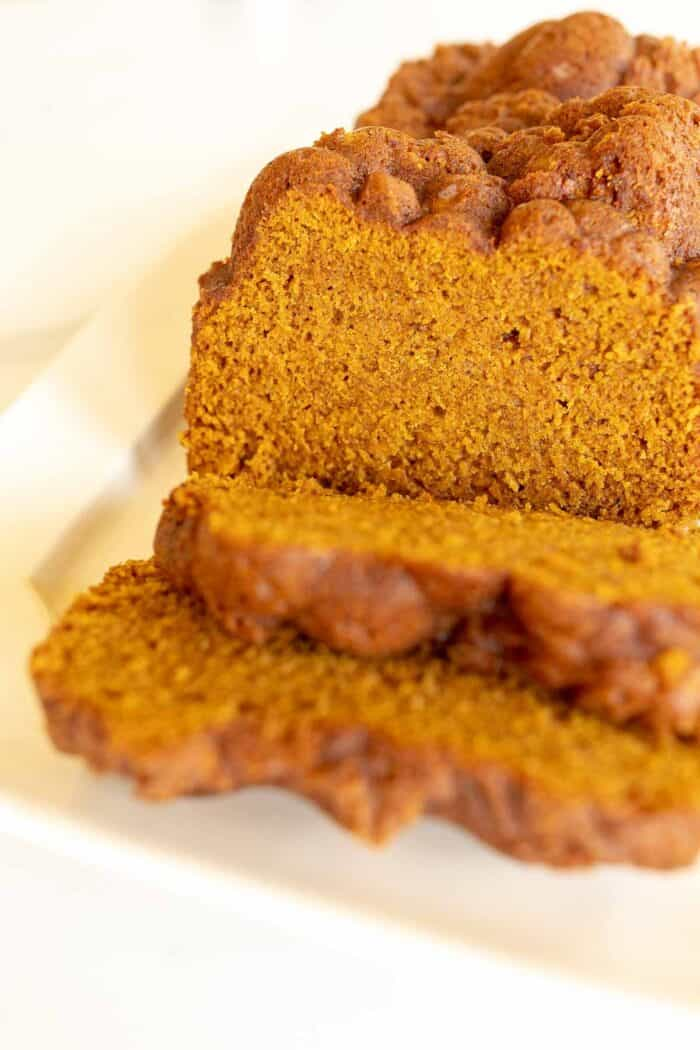 A white platter featuring a loaf of pumpkin bread with slices cut at the front.
