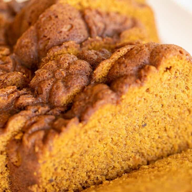 A white platter with a pumpkin bread recipe cut into slices
