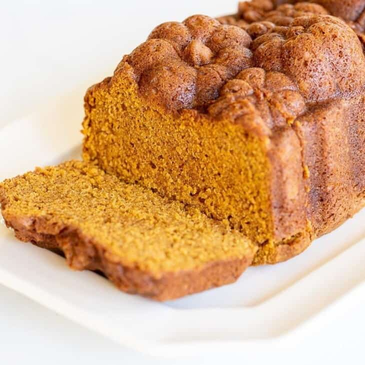 A white platter featuring a loaf of pumpkin bread with a slice cut at the front.