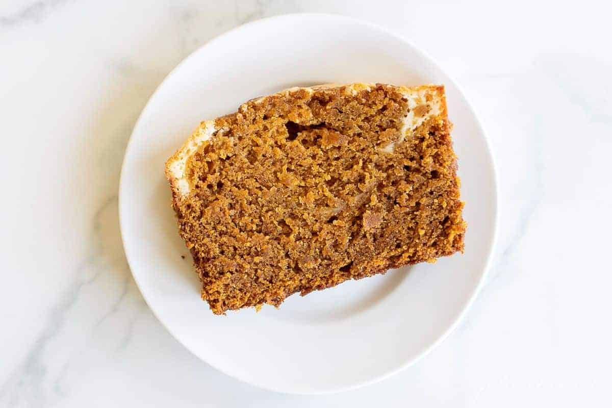 A marble surface with a small white plate with a slice of pumpkin cheesecake bread.