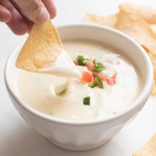 tortilla chip dipped in queso blanco dip in a white bowl