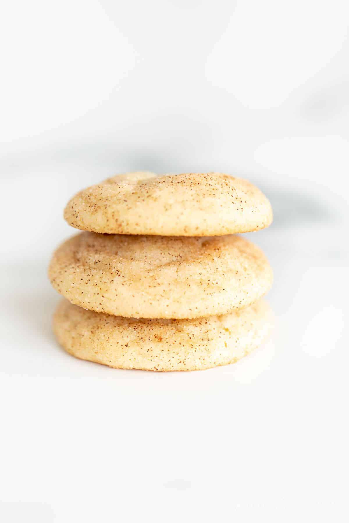 A stack of three snickerdoodle cookies without cream of tartar on a marble surface.