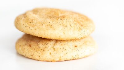 Two Snickerdoodle cookies without cream of tartar stacked on a white surface.