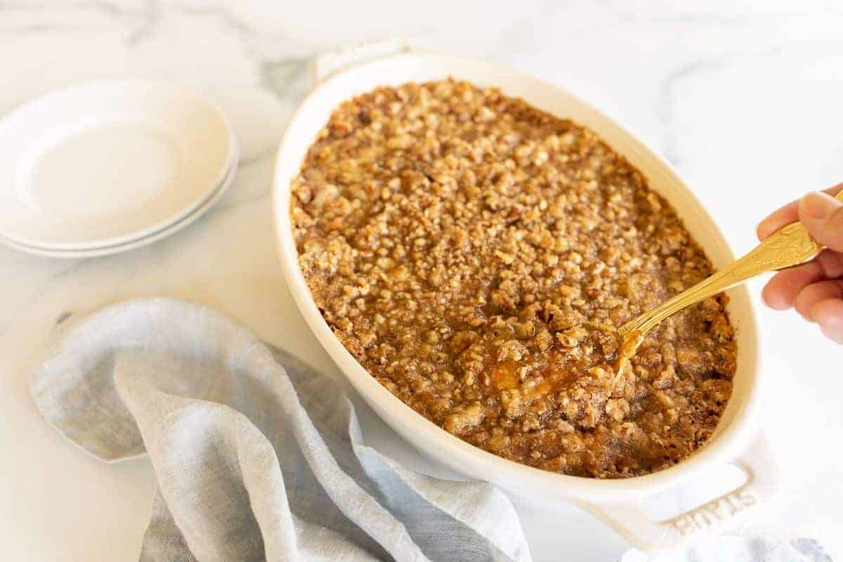 A white oval baking dish filled with a sweet potato casserole, spoon lifting out a serving.