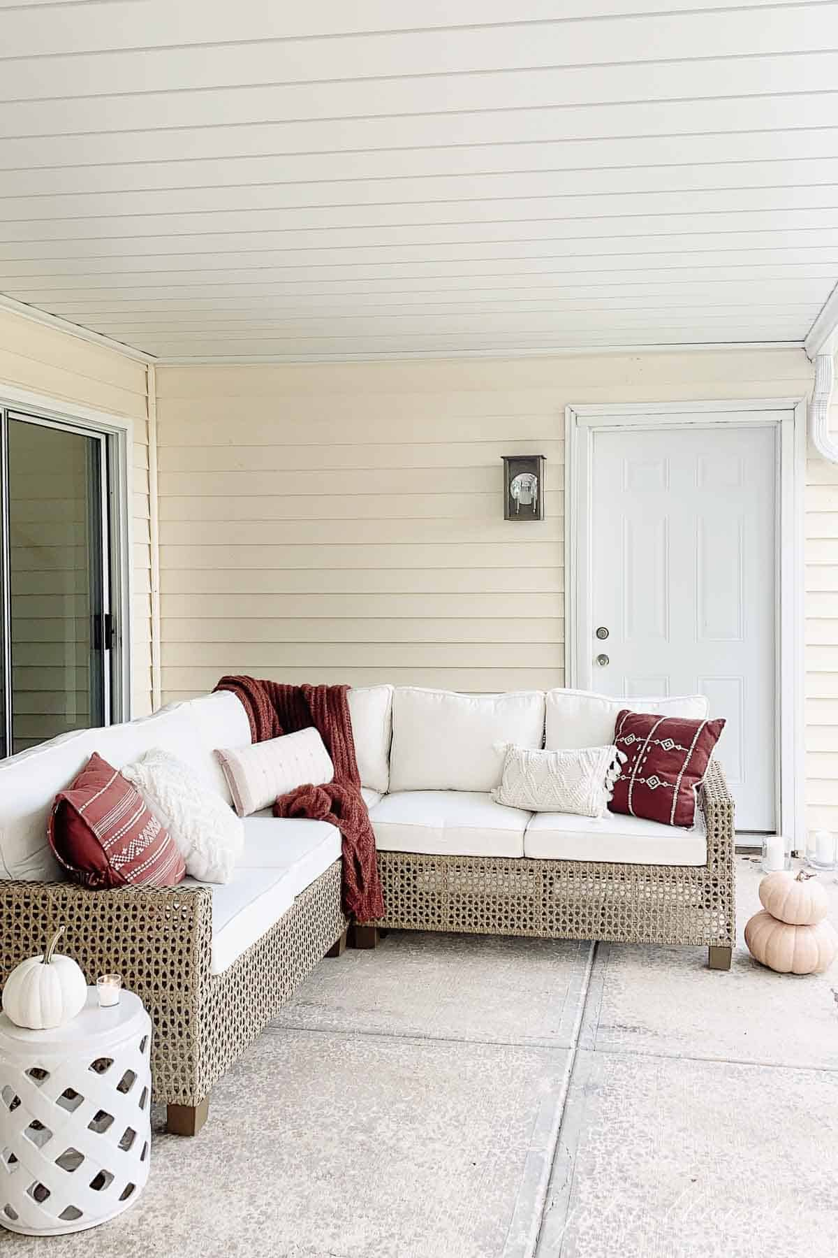 outdoor sectional with fall accents under a deck