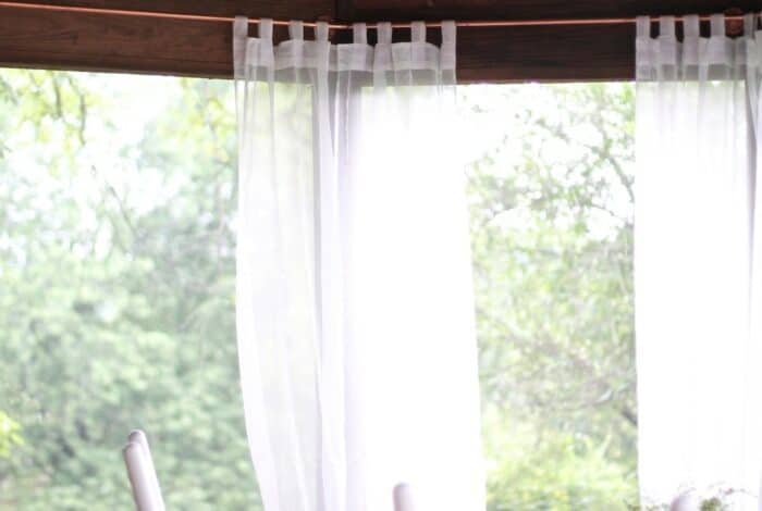 Diy copper curtain rods on a screened porch with white curtain panels.