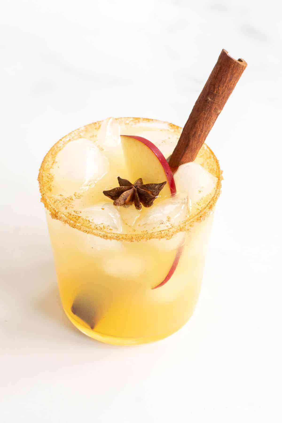 A clear glass with an apple cider margarita, rimmed in sugar and garnished with a cinnamon stick.
